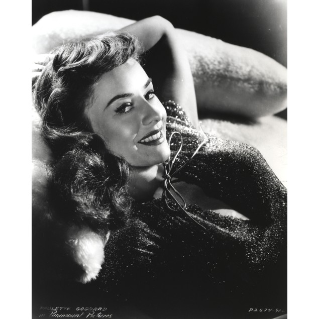 Paulette Goddard smiling while Lying on Couch in Glitter Dress Portrait Pos