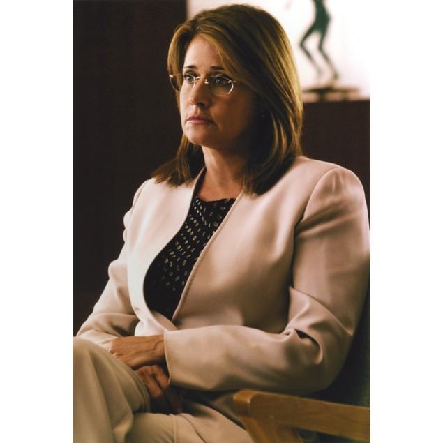 Lorraine Bracco sitting in White Blazer with Printed Blouse Under Poster