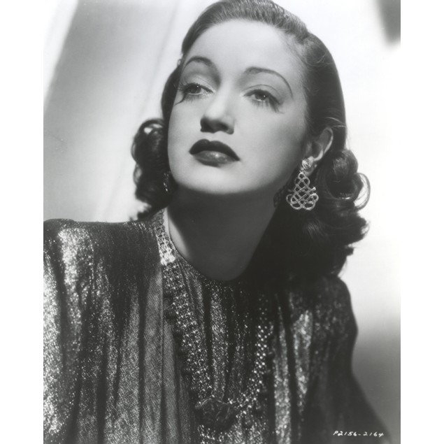 Dorothy Lamour wearing a metallic dress and earrings Poster
