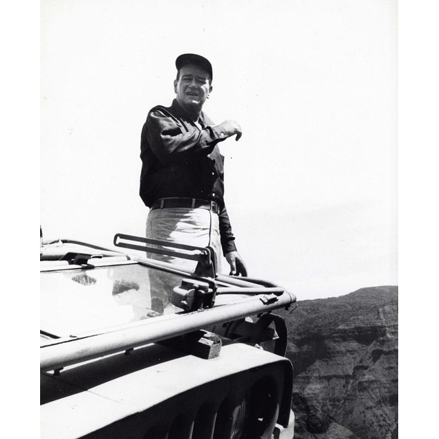 John Wayne standing behind a vehicle Poster
