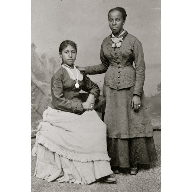 Portrait of two young African American women, one standing, one seated Post