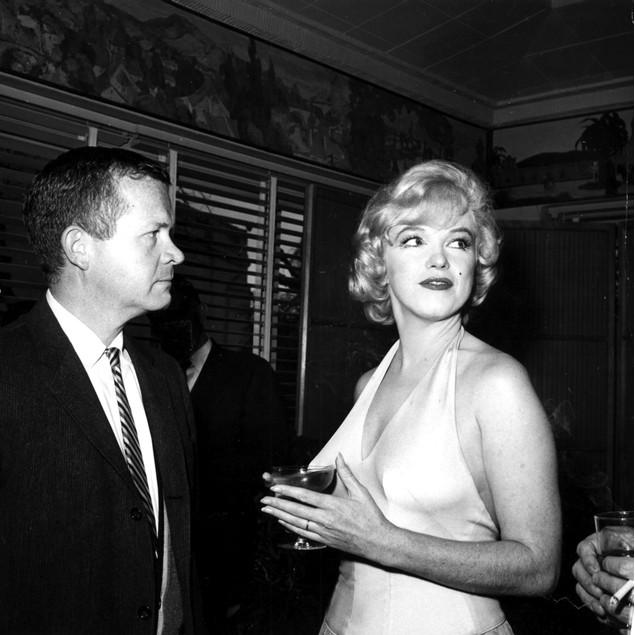 Marilyn Monroe and Bob Thomas at a social event Poster